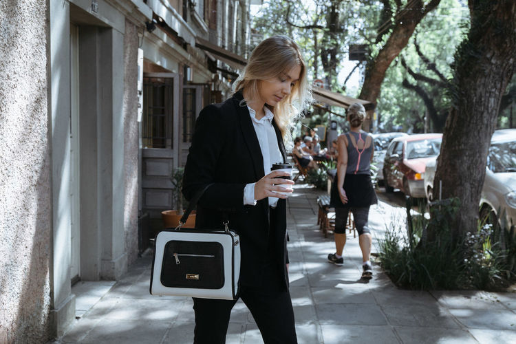 Businesswoman holding coffee cup while walking on footpath in city