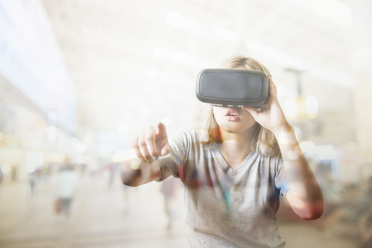 Multiple exposure of young woman looking through virtual reality simulator and airport