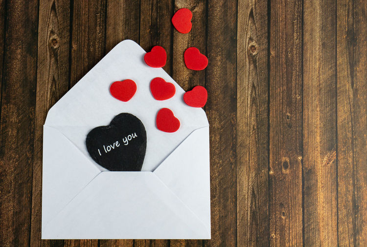 A white envelope with a black heart and the words I love you and red hearts, wooden table as a background Envelope Red White Wooden Valentines Letter Paper Background Day Love Design Holiday Heart Gift Decoration Symbol Concept Shape Celebration Romantic Greeting Romance Valentine Hearts Table Heart Shape Wood - Material Indoors  Still Life No People High Angle View Emotion Positive Emotion Art And Craft Creativity Close-up Text Directly Above White Color Group Of Objects