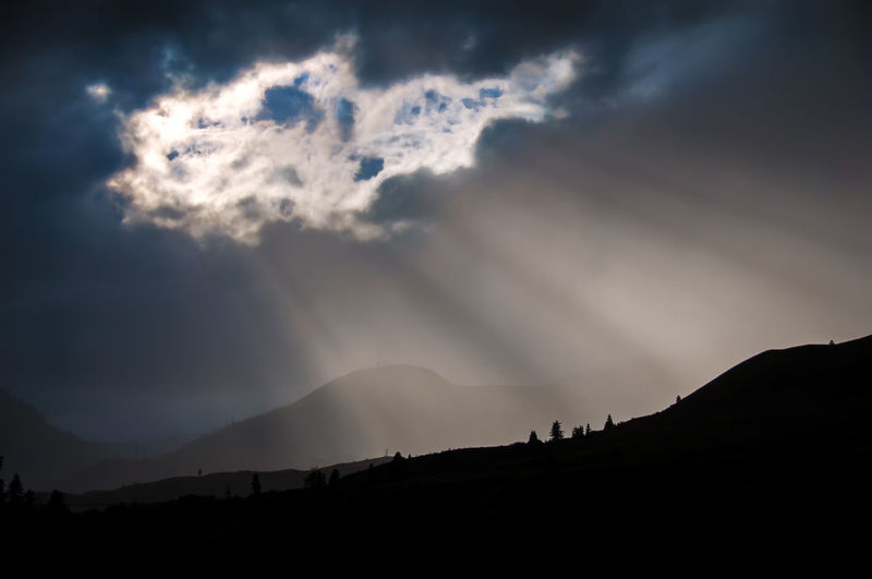 Scenic view of silhouette mountains against cloudy sky during sunset