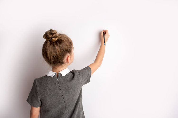 Rear view of girl standing against white background