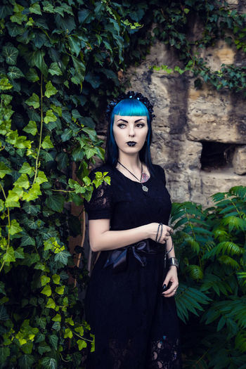 Beautiful goth girl with bright blue hair standing in the green ivy. on the eve of halloween