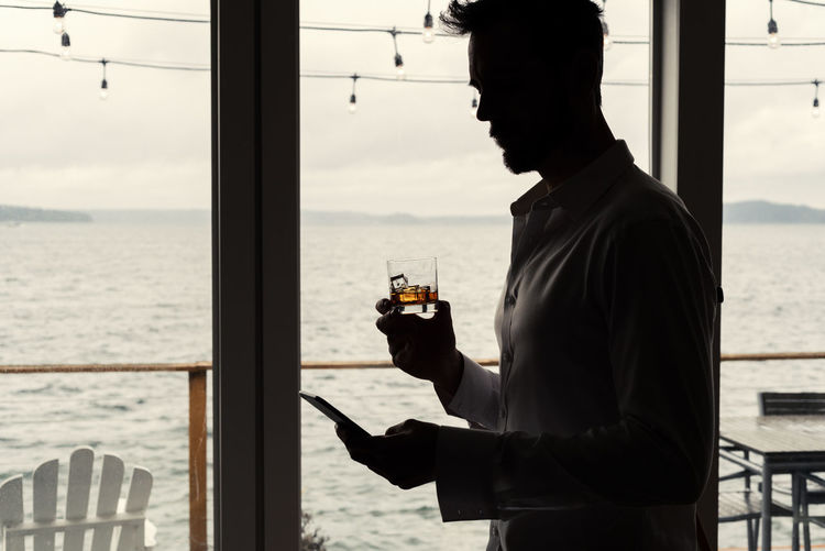 Man in silhouette reading smart phone while holding a alcoholic rocks glass drink at beach house with sea view. One Person Drink Refreshment Water Standing Food And Drink Real People Glass - Material Alcohol Window Glass Lifestyles Side View Sea Men Holding Leisure Activity Adult Outdoors Looking At View Drinking Silhouetted Whiskey Bourbon Scotch Vodka Rocks Glass Texting Reading Smart Phone Profile View Beach House