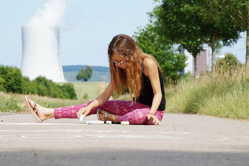Young woman drawing on road