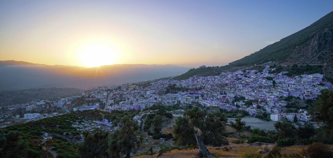 """""""The Blue City"""" - Sunset """"at the Spanish Mosque Chefchaouen Chefchaouen Medina Chefchaouen Blue City Morocco Travel Destinations Travel Travel Photography Digital Nomad Tourism Tourist Attraction  Tourist Destination EyeEmNewHere EyeEm Best Shots Sky Sunset Beauty In Nature Building Exterior Nature Scenics - Nature Mountain Architecture Environment Landscape Built Structure Plant City Sun Tranquility Tree Sunlight Town No People Tranquil Scene Outdoors Cityscape Lens Flare TOWNSCAPE"""