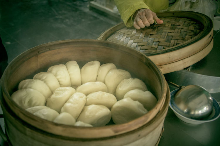 Midsection of person by dumplings in basket at kitchen