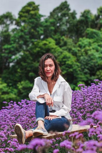 Portrait of smiling woman sitting on purple flowering plants