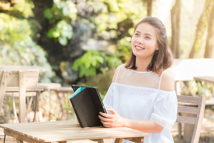 Smiling Young Woman Holding Digital Tablet While Sitting On Chair