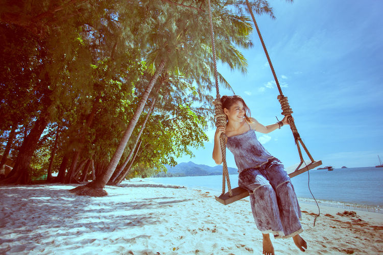 Woman on tree at beach against sky