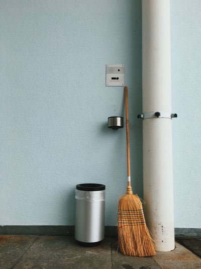 Broom And Dustbin By Wall