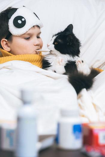 Sick child digital thermometer mouth fever illness headache.cat herbal tea taking temperature