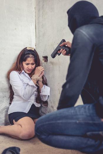 Burglar aiming handgun at woman in home