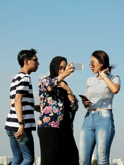 Leisure Activity Lifestyles Standing Friendship Togetherness Casual Clothing Bonding Communication Three Quarter Length Clear Sky Person Young Adult Blue Scenics Beauty In Nature People And Places Mobile Conversations Women Around The World