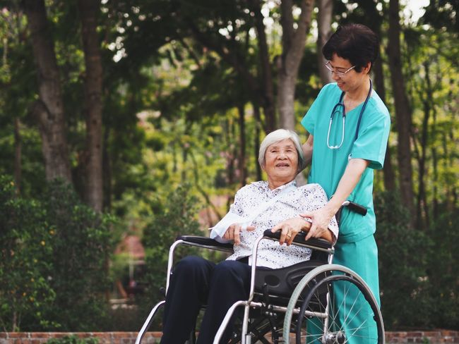 Senior nurse take care old woman sitting in wheelchair ,they're walking in the park. A Helping Hand Care Community Outreach Differing Abilities Doctor  Healthcare And Medicine Home Caregiver Nurse Outdoors Patient Physical Impairment Real People Recovery Retirement Senior Adult Senior Women Service Sitting Smiling Togetherness Tree Two People Wheelchair Women Young Women