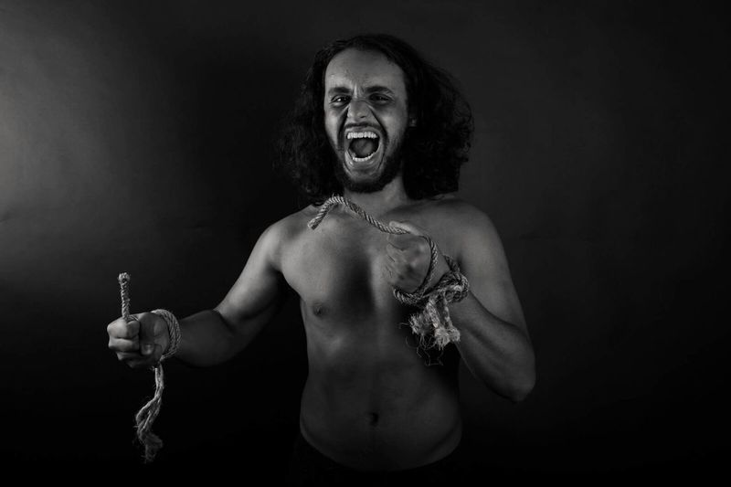 Portrait of furious man screaming against black background