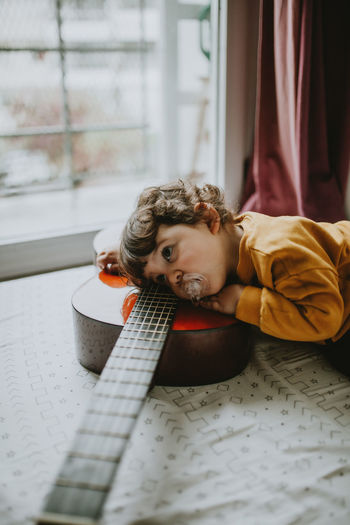 Portrait of child playing guitar at home