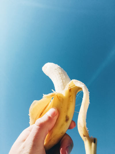 Close-up of hand holding banana against blue sky