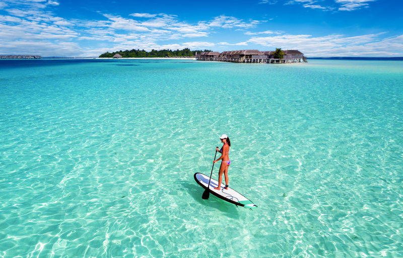 Woman on a SUP Board in the Maldives Adventure Aerial View Beach Beach Life Beauty In Nature Day Island Leisure Activity Maldives Nature Ocean One Person Outdoors Paddleboarding Paradise Sea Sky Sup Surfboard Turquoise Vacations Water Woman