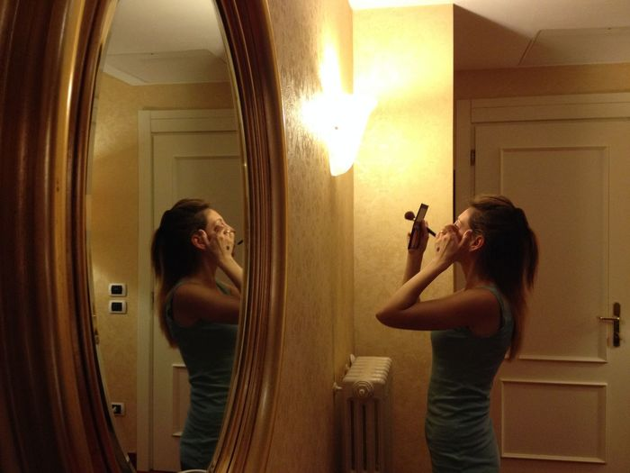 Reflection Of Woman On Mirror Doing Make-Up In Illuminated Room