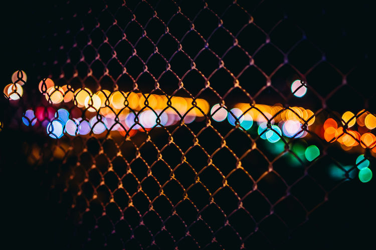 Close-Up Of Chainlink Fence Against Defocused Lights At Night