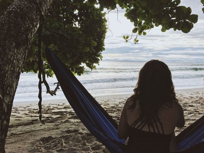 Rear view of woman sitting on hammock at beach