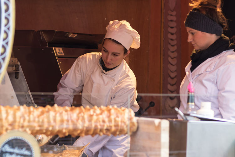 Sweet Berlin Christmas Market Baker - Occupation Bakery Chef Chef's Hat Commercial Kitchen Day Food Food And Drink Freshness Ready-to-eat Real People Small Business Smiling Streamzoofamily Streetphotography Sweet Food Two People Uniform Women Working Young Adult Young Women