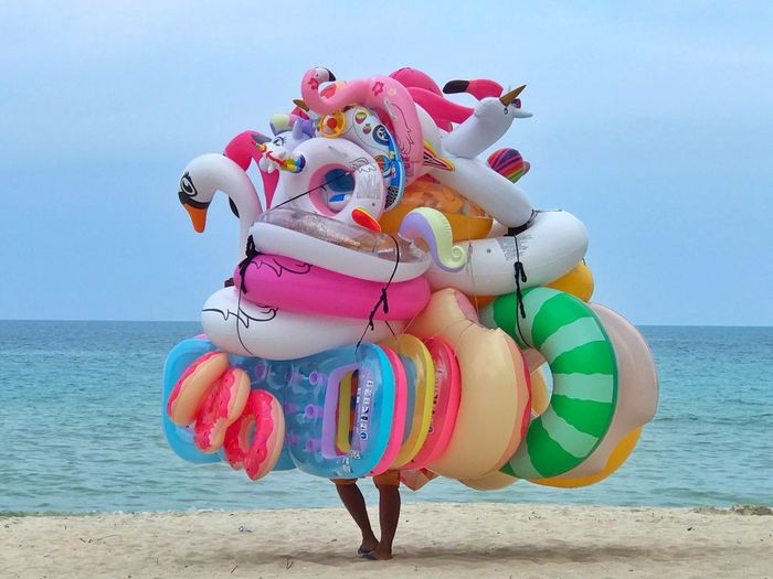 Full length of multi colored umbrellas on beach against sky