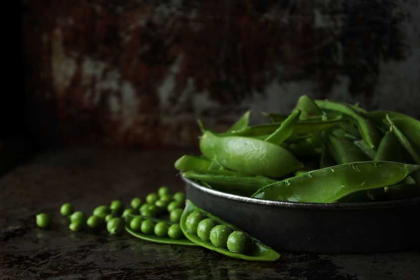 Peas in a pod Peas Freshness Shelling Peas Preparation  Agriculture Ripe Raw Green Color Snap Peas Copy Space Close Up Selective Focus Pod Pea Pod Food And Drink Healthy Eating Green Pea Wellbeing Vegetable Close-up Still Life Indoors  No People