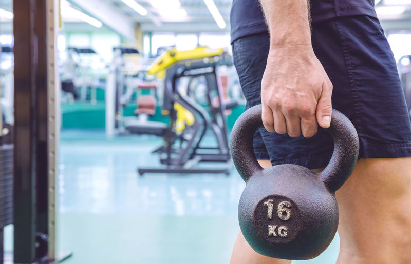 Midsection Of Man Holding Kettlebell