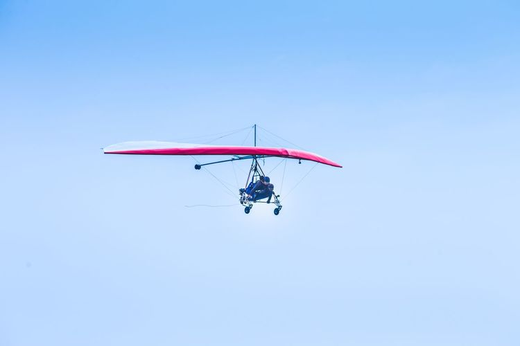 Low angle view of people hang gliding in sky