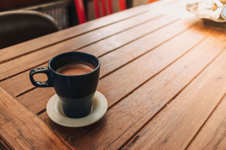 Blue mug of hot chocolate on wooden table in a cafe.