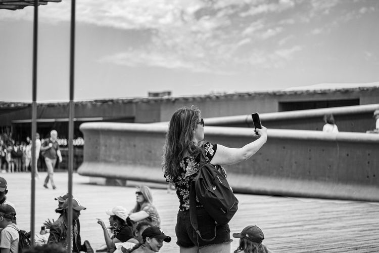 Rear view of woman photographing by railing against sky