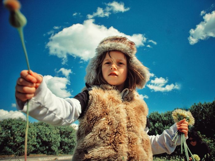 Portrait of girl with dandelions against sky