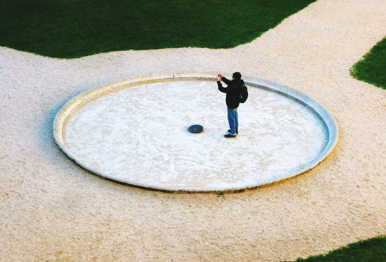 High Angle View Of Man Standing In Empty Fountain