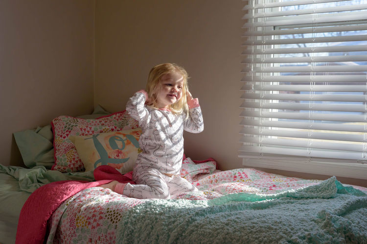 Cute blonde girl in morning sunlight in bedroom, just waking up on a new day Blonde Home Morning Natural Light Sunlight Waking Up Bed Bedroom Blond Hair Child Childhood Cute Day Early Front View Home Interior Little Girl Morning Routine One Person Preschooler Real People Rise And Shine Sitting