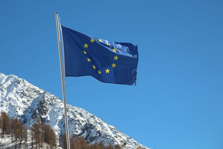 Low Angle View Of European Union Flag Against Snowcapped Mountain