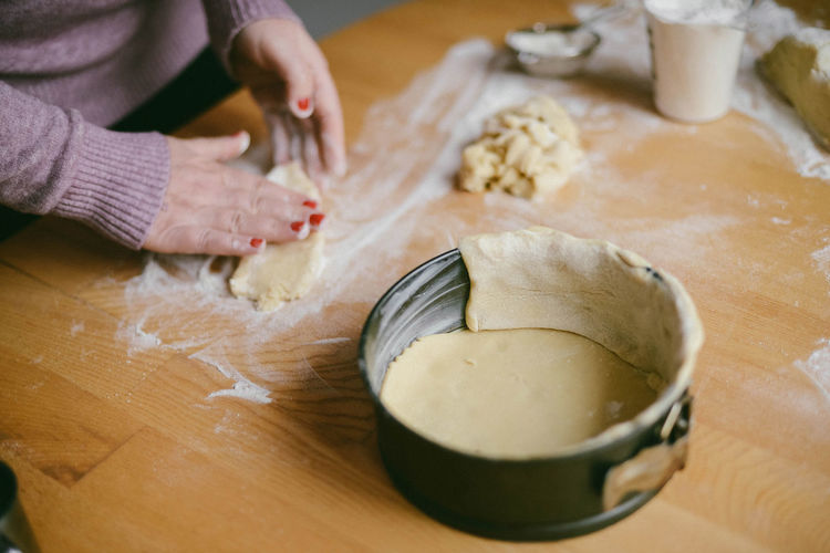 Midsection of woman preparing dough at table in kitchen