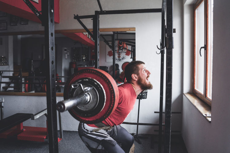 Man Lifting Barbell While Exercising At Gym