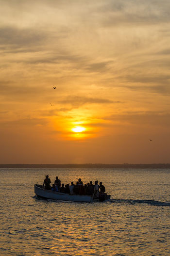Silhouette Of People In Boat On Sea Against Sky During Sunset, Bubaque, Bijagos Archipelago, Guinea-Bissau