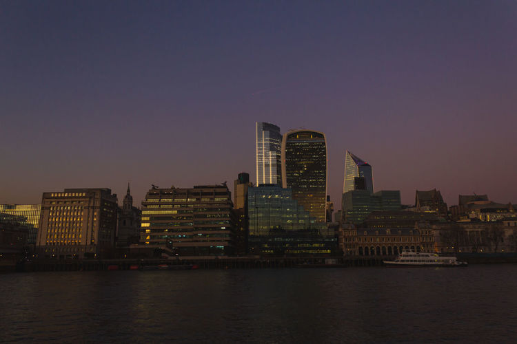Modern buildings by river against sky during sunset