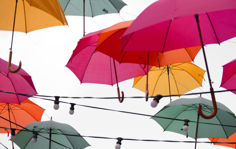 Low angle view of umbrellas hanging on umbrella against sky