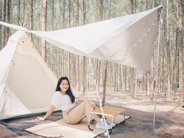 Happy asian teenage girl in front of camp tent. outdoor activity.