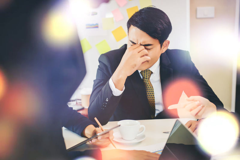 Stressed businessman sitting on table at office