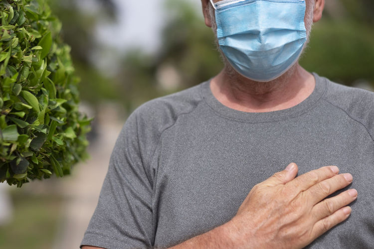 Midsection of senior man wearing mask standing outdoors