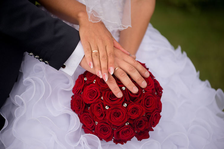 Midsection of women holding groom's hand