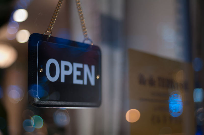 Close-up of open sign hanging from glass window of store