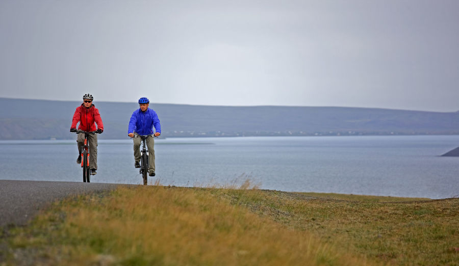 Rear view of men riding bicycle on shore against sky