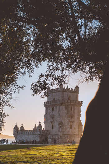 Belem tower during the golden hour Architecture Built Structure Travel Destinations Lisbon Portugal Europe Tree Plant History The Past Sky Building Exterior Nature Tourism Travel Ancient Outdoors Sunlight Building Sunset Day Silhouette Old Ruin Ancient Civilization