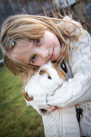 Portrait of girl carrying rabbit in yard