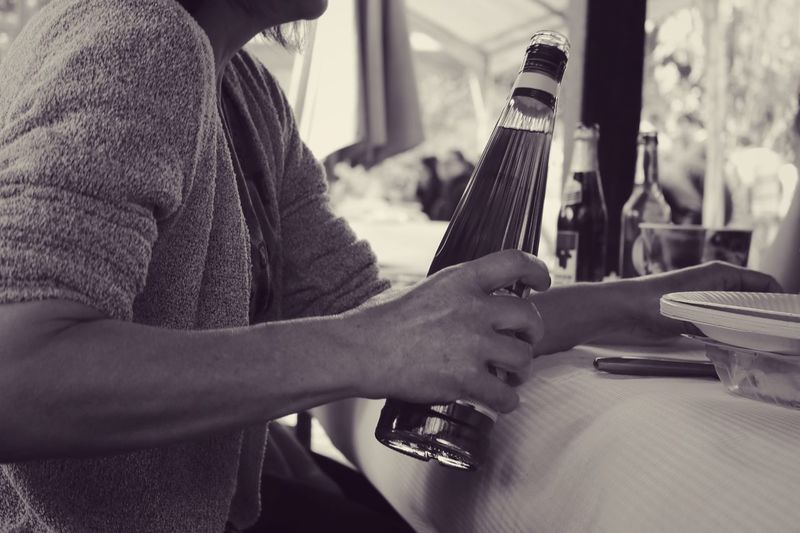 Midsection Of Woman Holding Bottle In Restaurant